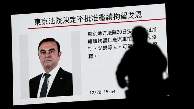 Un piéton passe devant un écran sur lequel est diffusé un programme sur le PDG de Renault et de l'Alliance Renault-Nissan Carlos Ghosn, à Tokyo, le 20 décembre 2018  [Behrouz MEHRI / AFP/Archives]