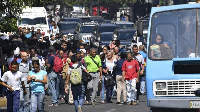 La population contrainte de marcher dans les rues, le métro étant arrêté en raison d'une panne de courant, le 25 mars 2019 à Caracas [YURI CORTEZ / AFP]