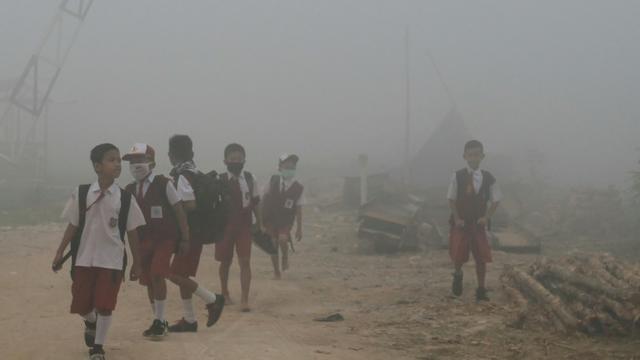 Des enfants indonésiens marchent vers leur école dans l'air pollué par de gigantesques incendies de forêt à Palembang, dans l'île de Sumatra, le 14 octobre 2019 [Abdul Qodir / AFP]