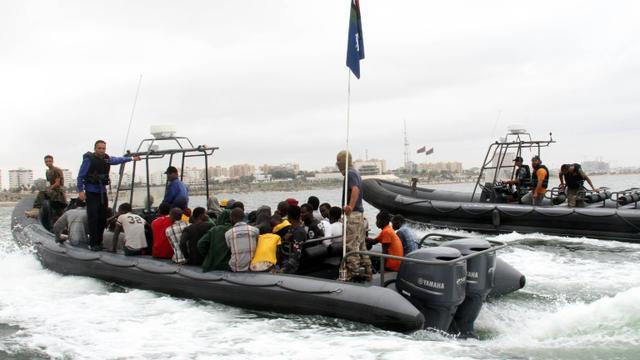 Des migrants dans un bateau des garde-côtes libyens après qu'ils ont été secourus au large de la ville de Qarabulli, à 60 km à l'est de Tripoli, le 7 septembre 2015 [ / AFP/Archives]
