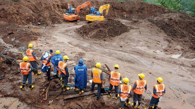Les secours s'activent après le glissement de train qui a ravagé le village de Malin, dans l'ouest de l'Inde, le 1er août 2014 [Indranil Mukherjee / AFP]