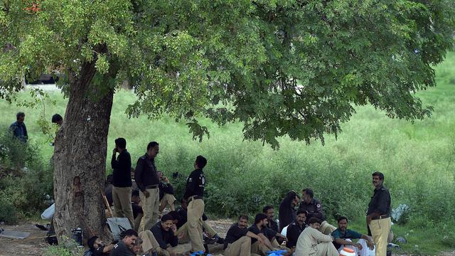 Des policiers pakistanais se reposent à l'ombre d'un arbre à Islamabad le 13 août 2014, où la situaiton est tendue à la veille de manifestations de l'opposition  [Aamir Qureshi / AFP]