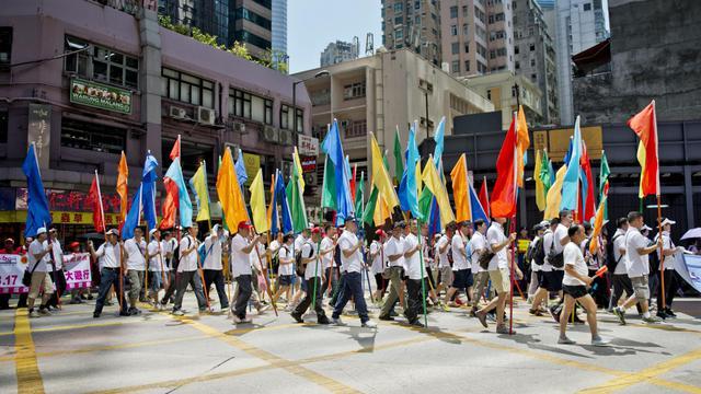 Des manifestants défilent à Hong Kong pour soutenir le gouvernement local contre un mouvement de désobéissance civile qui menace de paralyser la mégapole financière, le 17 août 2014 [Alex Ogle / AFP]