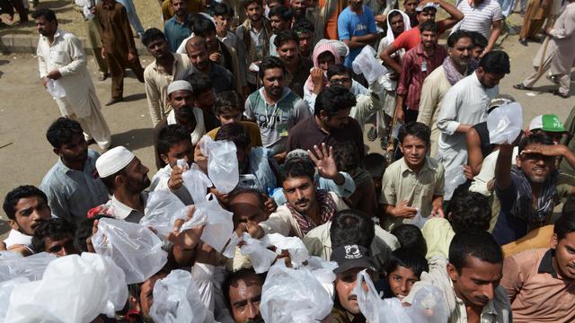Des partisans de l'opposant pakistanais Tahir-ul-Qadri rassemblés lors d'une distribution de nourriture pendant une manifestation anti-gouvernementale à Islamabad le 18 août 2014  [Farooq Naeem / AFP]