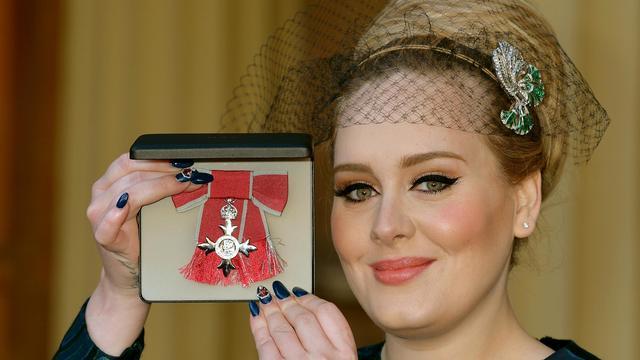 La chanteuse britannique Adele montre sa médaille après avoir été faite Membre de l'Ordre de l'Empire britannique (MBE), le 19 décembre 2013 à Londres [John Stillwell / Pool/AFP]