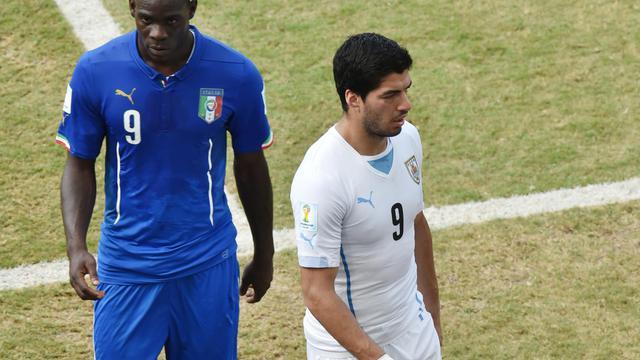 L'attaquant international italien du Milan AC Mario Balotelli (à gauche) à côté de l'attaquant uruguayen Luis Suarez (à droite) lors du match Italie-Uruguay du Mondial brésilien à Natal le 24  juin 2014 [Yasuyoshi Chiba   / AFP/Archives]