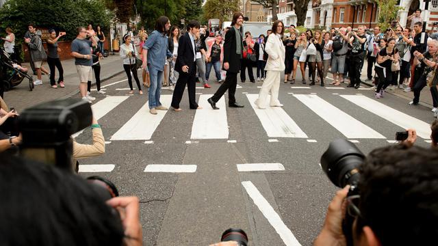"""La troupe de la comédie musicale """"Let it be"""" pose sur le fameux passage d'Abbey road, popularisé par les Beatles, le 8 aout 2014 à Londres pour marquer le 45e anniversaire de la photographie [Leon Neal / AFP]"""