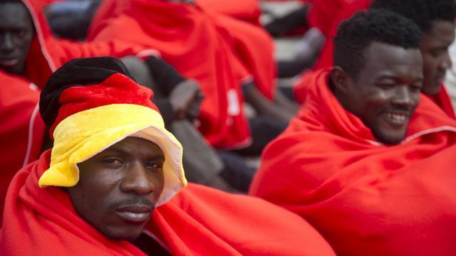 Des immigrés clandestins en provenance d'Afrique secourus par les garde-côtes espagnols enveloppés dans des couvertures de la croix-rouge dans le port de Tarifa le 11 août 2014 [Marcos Moreno / AFP]