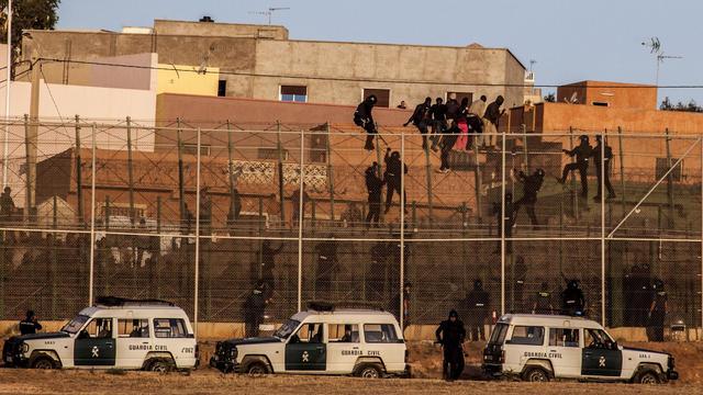 Des membres des garde civile espagnole grimpent sur la barrière, alors que des migrants d'Afrique tentent d'enter dans l'enclave espagnole de Melilla le 14 août 2014 [Jose Colon / AFP]