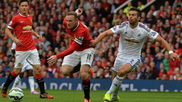 L'attaquant anglais de Manchester United Wayne Rooney à la lutte avec le défenseur de Swansea Jordi Amat lors d'un match comptant pour la 1re journée de championnat d'Angleterre, le 16 août 2014 à Old Trafford, Manchester. [Paul Ellis / AFP]