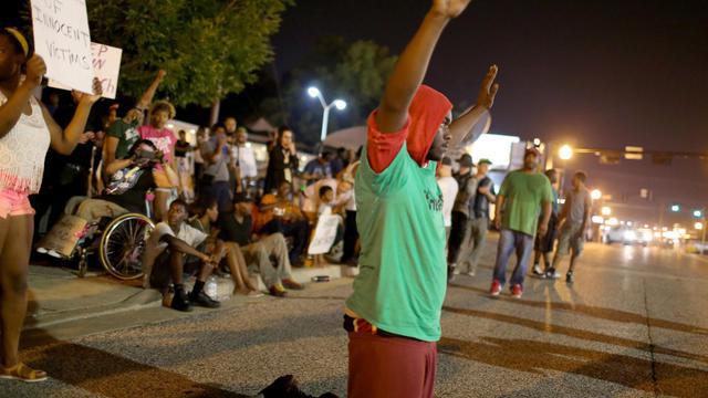 Un manifestant s'agenouille sur la route lors d'un rassemblement pour réclamer justice après la mort de Michael Brown, à Ferguson le 22 août 2014 [ / Getty/AFP]