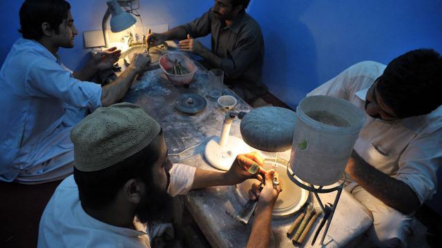 Des ouvriers pakistanais taillent, polissent des pierres précieuses dans un atelier à Peshawar, le 24 juin 2014 [Hasham Ahmed / AFP]