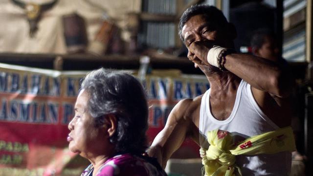 Le chamane malaisien Zailani Che Moh (d) administrant un traitement à la patiente Che Esa dans le village de Tanah Merah, près de Kota Bharu, en Malaisie, le 8 juin 2014 [Manan Vatsyayana / AFP]