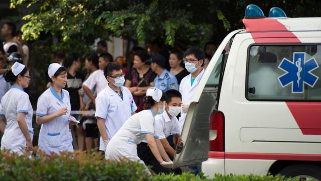 Des médecins et infirmiers chinois au secours d'une victime de l'explosion d'une usine à Kunshan, le 2 août 2014 [Johannes Eisele / AFP]