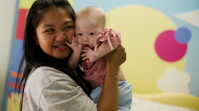 La mère porteuse thaïlandaise Pattaramon Chanbua tient le petit Gammy, enfant trisomique, dans ses bras à l'hôpital Samitivej, dans la province Chonburi le 4 août 2014 [Nicolas Asfouri / AFP/Archives]