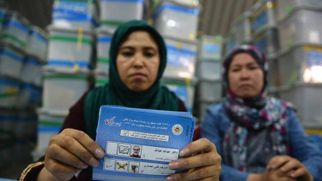 Des membres de la commission éléctorale afghane exhibent des bulletins de vote, le 4 août 2014 à Kaboul [Shah Marai / AFP]