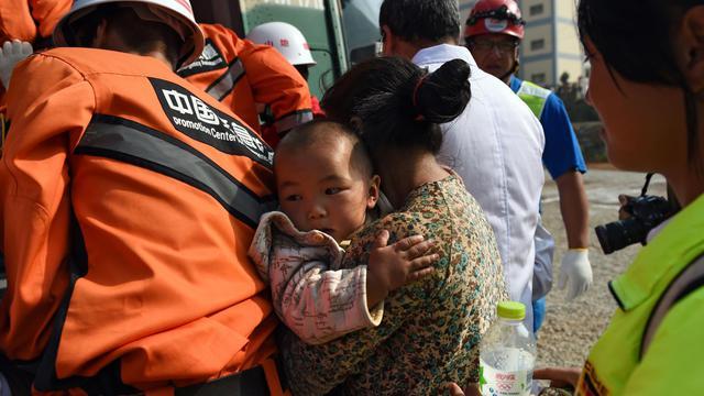 Une femme tente de monter dans un hélicoptère, le 6 août 2014 à Longtoushan, alors que des survivants du séisme du 3 août sont évacués par hélicoptères militaires  [Greg Baker / AFP]