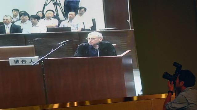 Le détective britannique Peter Humphrey dans le box des accusés au tribunal de Shanghai, sur un écran retransmettant le procès pour la presse, le 8 août 2014 [Johannes Eisele / AFP]