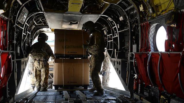 Des soldats américains chargent des cartons à bord d'un hélicoptère Chinook sur la base militaire de Bagral, à 50km au nord de Kaboul, le 11 août 2014 [Shah Marai / AFP]