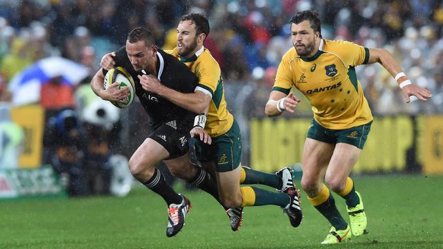 Le demi d'ouverture de la Nouvelle-Zélande, Aaron Cruden, taclé par l'Australien Nic White lors du match d'ouverture du Four Nations, le 16 août 2014 à Sydney. [William West / AFP]