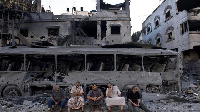 Des Palestiniens devant un bâtiment détruit par un raid israélien à Gaza, le 20 août 2014 [Roberto Schmidt / AFP]