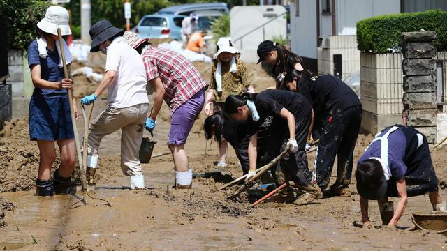 Des habitants enlèvent la boue de la route à Hiroshima le 21 août 2014 après des glissements de terrain  [ / Jiji Press/AFP]