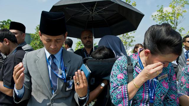 Des membres de la Malaysia Airlines prient et pleurent, le 22 août 2014 à l'arrivée des corps des personnes tuées dans le crash du vol MH17 au-dessus de l'Ukraine [Mohd Rasfan / AFP]