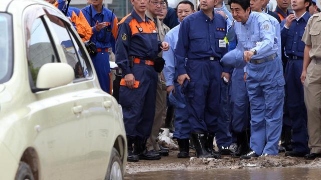Le Premier ministre Shinzo Abe (à droite) inspecte les dégâts provoqués par les glissements de terrain  qui ont fait 52 morts et 28 disparus, à Hiroshima (Japon), le 25 août 2014 [Jiji Press / JIJI PRESS/AFP]