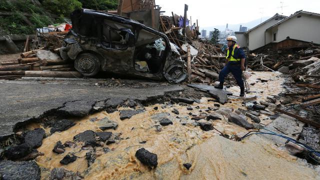 Un sauveteur recherche des personnes disparues dans des glissements de terrain à Hiroshima (Japon) le 26 août 2014 [Jiji Press / JIJI PRESS/AFP]