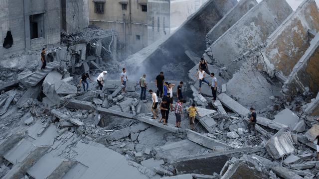 Des Palestiniens inspectent les restes d'un immeuble détruit par une attaque israélienne à Gaza, le 26 août 2014 [Mohammed Abed / AFP]