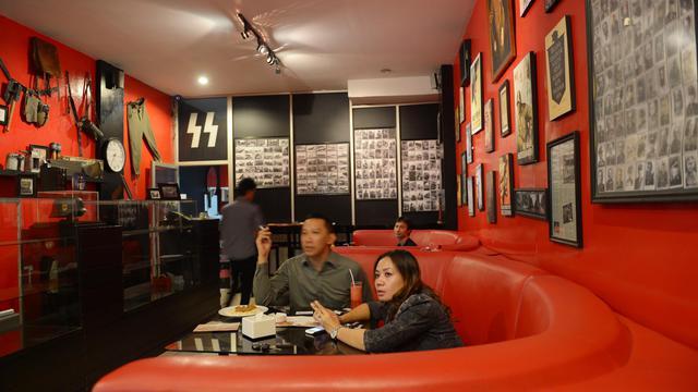 """Des clients dînent à une table du """"Soldaten Kaffee"""", un café d'inspiration nazie établi à Bandung en Indonésie [Adek Berry / AFP]"""