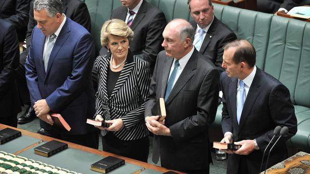 Le Trésorier australien Joe Hockey (g) prête serment, avec plusieurs responsables politiques dont le Premier ministre Tony Abbott, à l'ouverture de la 44ème session du parlement, à Canberra, le 12 novembre 2013 [Mark Graham / AFP/Archives]