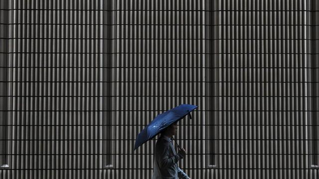 Un homme marche sous la pluie à Hong Kong le 10 mai 2014 [Dale de la Rey / AFP/Archives]