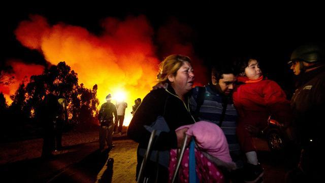 Des habitants fuient leur quartier ravagé par les flammes le 13 avril 2014 à Valparaiso [Martin Bernetti / AFP]
