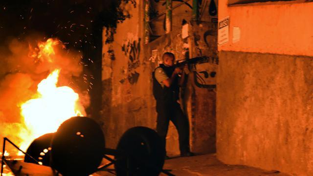Un policier patrouille une favela en proie à des émeutes, près du quartier touristique de Copacabana, à Rio de Janeiro, le 22 avril 2014 [Christophe Simon / AFP]