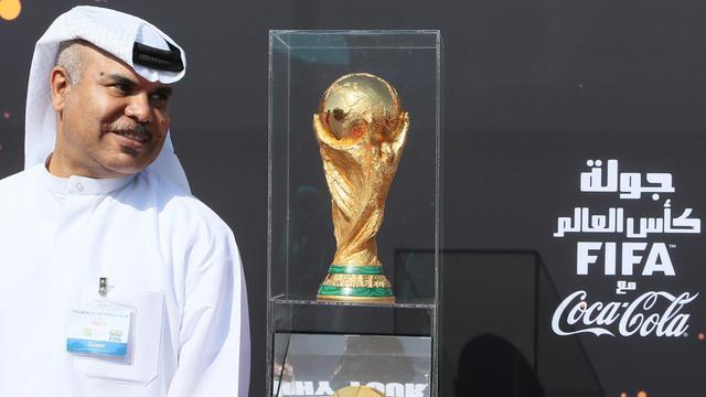 Le 12 décembre 2013, un représentant du Qatar pose à côté de la Coupe du Monde présentée dans le cadre d'une tournée mondiale au Qatar, futur hôte de la compétition en 2022 [ / AL-WATAN DOHA/AFP/Archives]