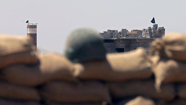 Un drapeau de l'Etat islamique (EI) flotte face à une position tenue par les Peshmerga, les soldats kurdes, le 26 juin 2014 à Sulaiman Bek, entre Bagdad et Kirkouk [Karim Sahib / AFP/Archives]