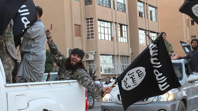 Image extraite du média jihadiste Al-Baraka news, le 11 juin 2014, montrant des militants de l'EI et leur drapeau noir dans la ville syrienne de Raga  [- / Welayat Raqa/AFP/Archives]