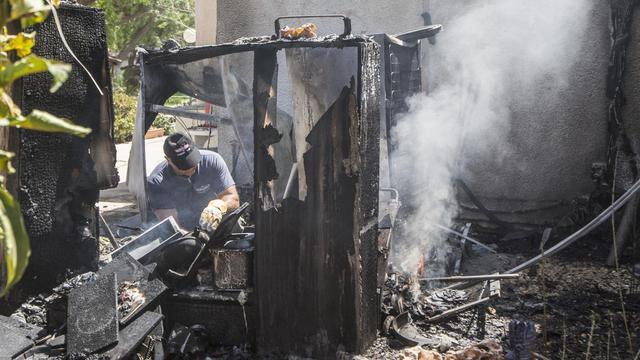Un expert israélien éteint l'incendie provoqué par la chute d'une roquette palestinienne sur Kfar Aza, le 14 juillet 2014 [Jack Guez / AFP/Archives]