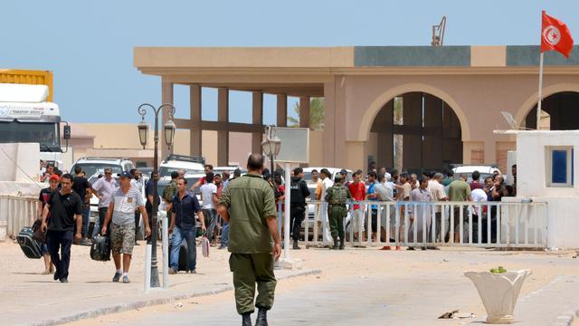 Des réfugiés venant de Libye passent un poste frontière tunisien, le 30 juillet 2014 [F. Nasri / AFP]
