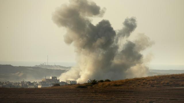 De la fumée s'échappe d'une maison à la frontière entre la bande de Gaza et Israël après une frappe israélienne, le 3 août 2014 [Thomas Coex / AFP]