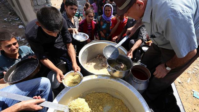 Des familles irakiennes de la communauté yazidie déplacées dans la ville de Sinjar au nord de l'Irak, reçoivent des distributions de nourriture dans la ville kurde de Dohuk, le 5 août 2014 [Safin Hamed / AFP]