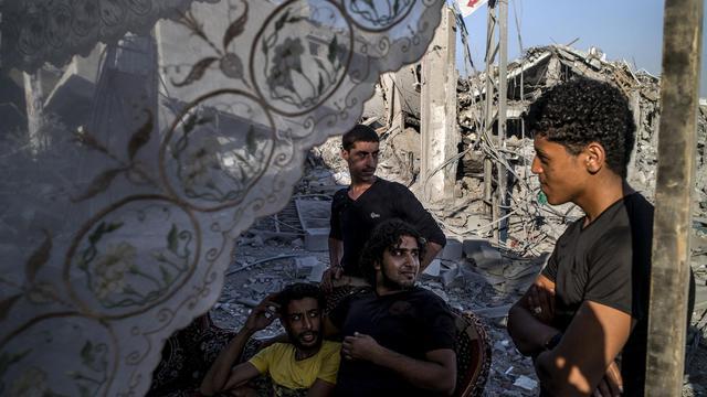 Des Palestiniens devant une maison détruite à Shejaiya à Gaza le 6 août 2014 [Marco Longari / AFP]
