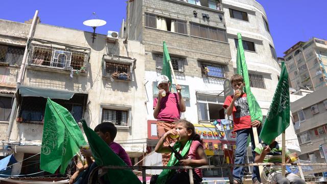 Les drapeaux verts du mouvement islamite Hamas portés par des enfants à Gaza le 7 aout 2014, au troisième jour de la trève avec Israel, que le mouvement islamiste a décidé de ne pas poursuivre [Roberto Schmidt / AFP]