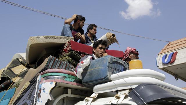 Des réfugiés syriens ont entassé leurs affaires dans un camion et traversent le village de Labwek dans la plaine de la Bekaa, le 7 août 2014 après avoir fui Arsal [Joseph Eid / AFP]