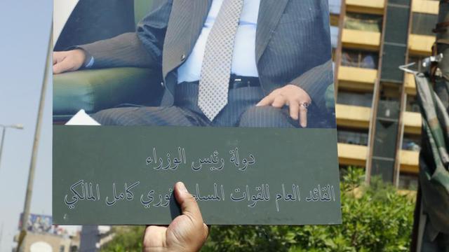 Un Irakien brandit une pancarte avec la photo de Nouri al-Maliki, le 9 août 2014 à Bagdad [Sabah Arar / AFP]
