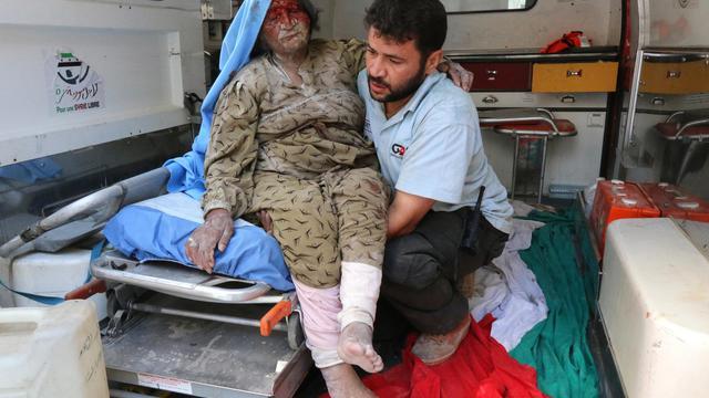 Un homme aide une femme blessée après une attaque aérienne attribuée au gouvernement syrien, le 9 août 2014 dans le district d'Alep (nord)  [Zein Al-Rifai / AMC/AFP]