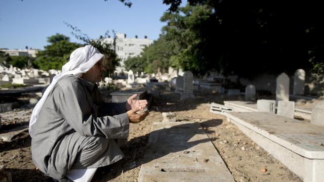 Hamed Abou Chabab, qui avait fui la guerre en Syrie pour trouver refuge dans la bande de Gaza, prie le 7 août 2014 au cimetière de Gaza City sur la tombe de son fils, emporté par une bombe israélienne  [Mahmud Hams / AFP]