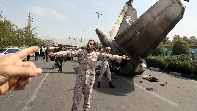 Des gardiens de la révolution et de membres des forces de sécurité iraniennes sur le site du crash près de l'aéeoport Mehrabad de Téhéran, le 10 août 2014 [Atta Kenare / AFP]