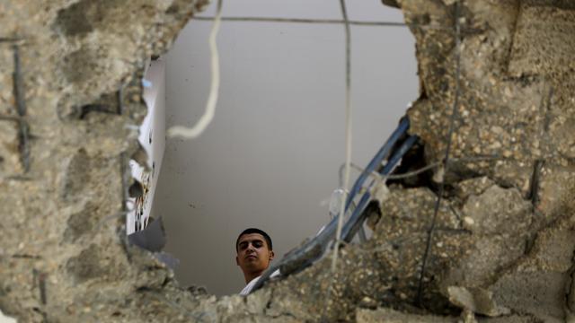 Un Palestinien de la famille Al-Elaa regarde le trou géant dans sa maison, dans le camp de réfugié de Jabalia à Gaza, le 10 août 2014 [Mohammed Abed / AFP]
